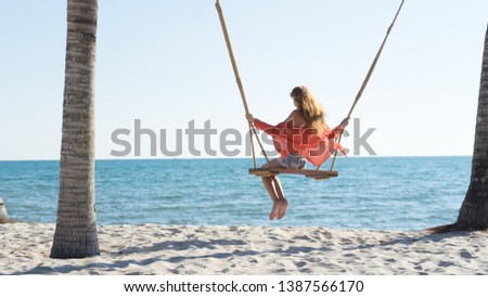 Vacation concept. Young woman swing on a beach swing. Happy traveller women on the Phu Quoc beach #1387566170