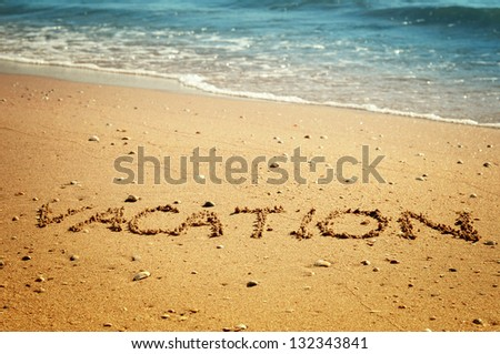 """Vacation"" written in the sand on the beach blue waves in the background"