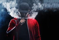 vaping man holding a mod. A cloud of vapor. Black background.