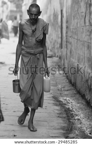 VARANASI, INDIA - NOVEMBER 27: A poverty-stricken man walks down the street in Varanasi, India, on November 27, 2008.  Varanasi, once a center of silk sari production, is in an economic slum.