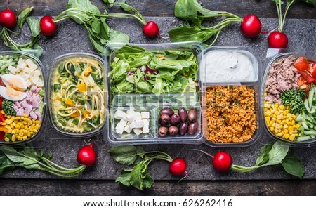 Variety of clean dieting salads in  plastic package and green measuring tape on rustic background, top view. Healthy clean food concept.