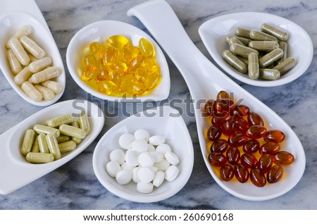 Variety of dietary supplements, including capsules of Garlic, Evening Primrose Oil; Artichoke Leaf;  Olive Leaf; Magnesium and Omega 3 Fish Oil.Selective focus. Taken in daylight. Stock photo ©
