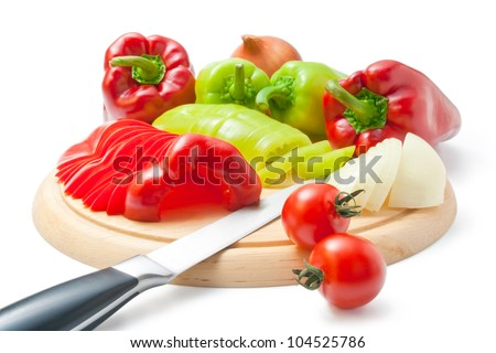 Vegetables. Fresh ripe red and green peppers and onions placed on a wooden cutting board and around arranged with kitchen knife and some cherry tomatoes isolated on white background.