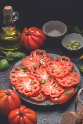 Vegetarian salad caprese  with Italian Oxheart tomatoes (Cuore di Bue), olives oil , basil and spacy papper. Simple summer  appetizer plate, cutlery and ingredients on dark rustic background