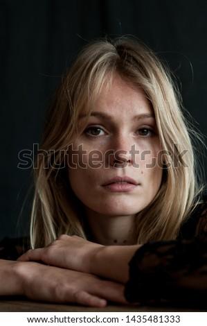 vertical close up studio  headshot of blond nordic woman with brown eyes with melancholic expression on sad face with black background and natural light