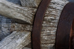 very Close look of a weathered old  cracked and rusted woodened spoked wagon wheel with axle and hub reinforce with metal rings