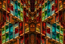 Very colorful building projected in an artistic, symmetrical form. It gives the effect of a kaleidoscope. There are many balconies and windows which are multicolored and with attractive pattern.