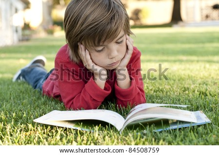 Very cute 7 year old boy lying on the grass reading a kids book