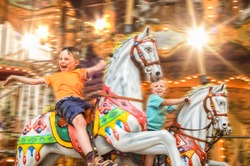 Very happy children ride in a nostalgic horse carousel that is deliberately blurred by movement