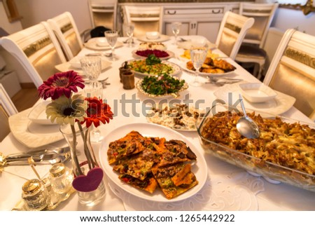 very nicely prepared dining table for special, valentines' day or Ramadan or Christmas in the luxury living room. Pasta,macaroni,salads,pizza on the table for party time.