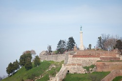 Victor statue on Kalemegdan fortress, seen from lower kalemegdan park during a afternoon. Located in Kalemegdanski park, it's a landmark of the city.