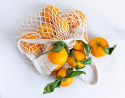 View from above. Tangerines in a white string bag on a white background. Modern reusable shopping, waste-free concept. Selective focus.