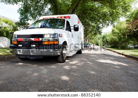 3/4 view of an ambulance parked in a residential area of a city - stock photo