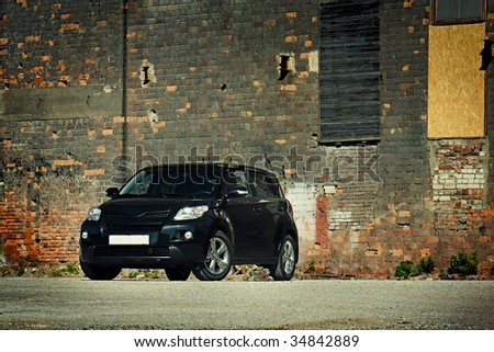 3/4 view of modern crossover vehicle near old brick wall #34842889