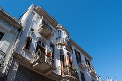 view of old building with wooden shutters and balconies with railings in the old city