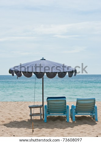 view of two chairs and umbrella on the beach