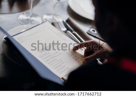 Viewing the menu in the restaurant. Food menu. Man see the food menu.  Order food through the menu.