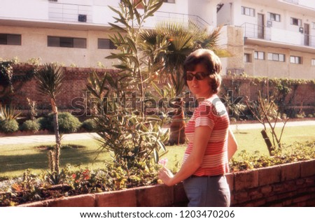 1974 vintage analog photo of a young pregnant woman enjoying the sun on her balcony during a holiday in Torremolinos, Spain.