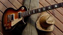 vintage electric guitar and cowboy hat closeup on the wooden boards