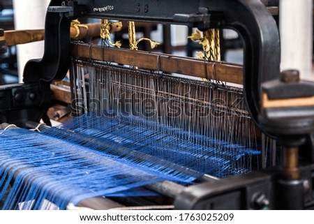 Vintage old loom weaving machine close up. Old Textile Machine. A loom machine for clothing or woven label. Yarn thread lines on the weaving loom machine for clothing  in textile or garment factory.  Photo stock ©