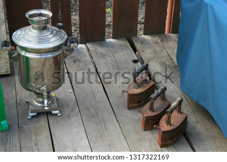2009.08.29, Vladimir, Russia. composition of a samovar and old cast iron irons. Still life in village.