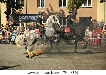 VRATIMOV, CZECH REPUBLIC-SEPTEMBER 7: Mounted policemans jumping across the fire.rescue and emergency services open day. Units at car crash training on September 7, 2013 in VRATIMOV, Czech republic.