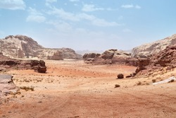 Wadi Rum desert, Jordan,  The Valley of the Moon. Orange sand, haze, clouds. Designation as a UNESCO World Heritage Site. National park outdoors landscape. Offroad adventures travel background.