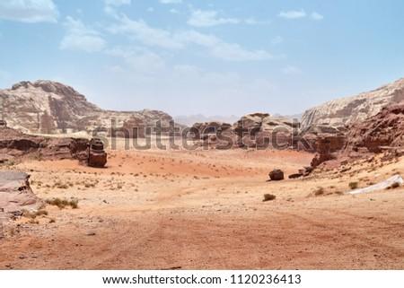 Wadi Rum desert, Jordan,  The Valley of the Moon. Orange sand, haze, clouds. Designation as a UNESCO World Heritage Site. National park outdoors landscape. Offroad adventures travel background.     #1120236413