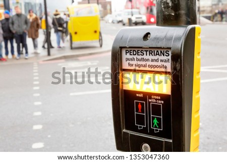 """Wait"" sign at pedestrian crossing in the City of London, UK. Crosswalk button for pedestrians. Blurred pedestrians on background. #1353047360"