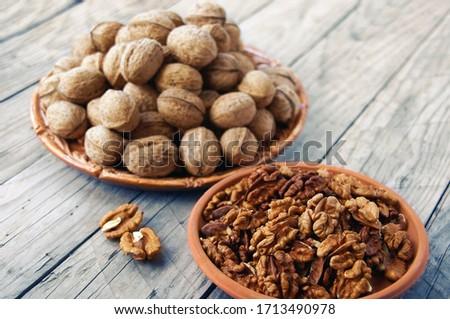 Walnuts in a ceramic plate and walnut kernels in a clay plate on a wooden table. Two ceramic plates in walnuts on a wooden table. Wood background.