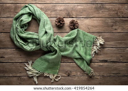 warm scarf on rustic with pine corn wooden background. Top view