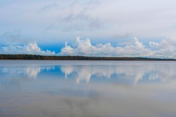 water smooth surface of the lake. reflection of the sky in the water.the concept of calmness and relaxation