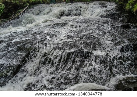 waterfall, mountain stream, with strongly and rapidly falling with splashes down, with rocks on a summer day.