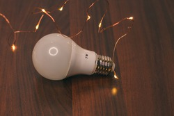 7-watt led energy-saving frosted light bulb and yellow Christmas lights isolated on wooden background. The concept of saving energy