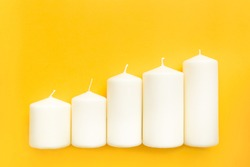 Wax candles on a yellow background, located a ladder. Concept upward curve. Schedule.