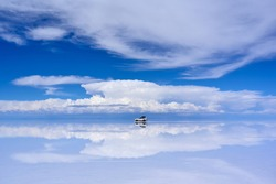 4WD car driving on the mirror surface of Uyuni Salt Flat with the reflection of sky and cloud, Bolivia