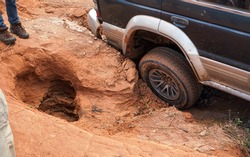 4wd vehicle driving over road with extreme holes and bumps, close up on rear wheel - roads are in very bad conditions in Andringitra, Madagascar, especially after rain
