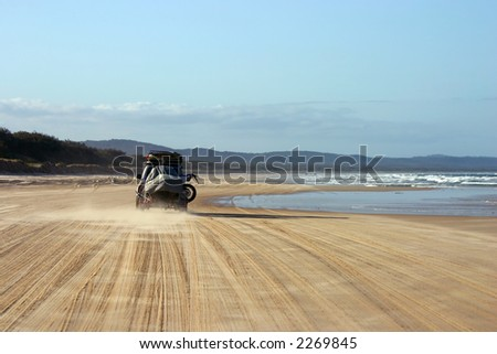 4WD vehicule driving on the beach with a trailer (Fraser Island, Australia)