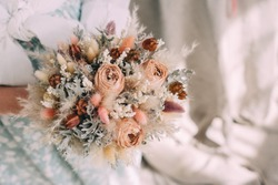 wedding bouquet of dried flowers in the hands of a florist