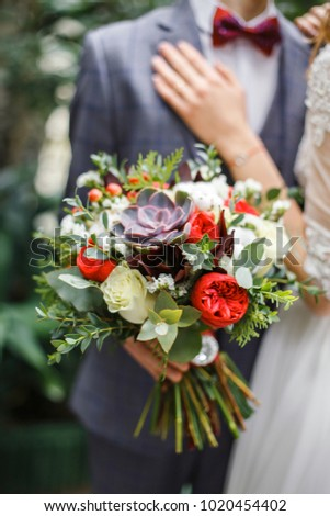 wedding bouquet on the background of the bride and groom #1020454402