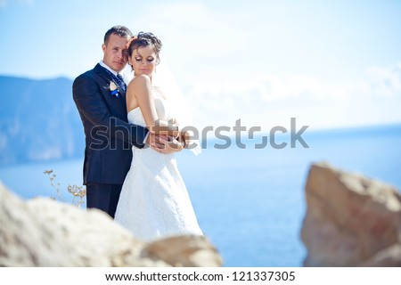 wedding: bride and groom by the sea - stock photo