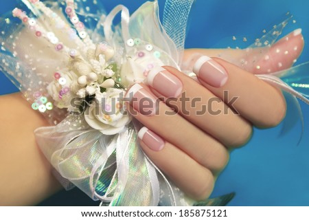 Wedding manicure on female hand with festive decoration of white ribbons and flowers