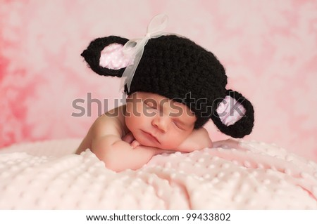 2 week old newborn girl wearing a black crocheted black sheep hat sleeping on a pink blanket with a pink background.