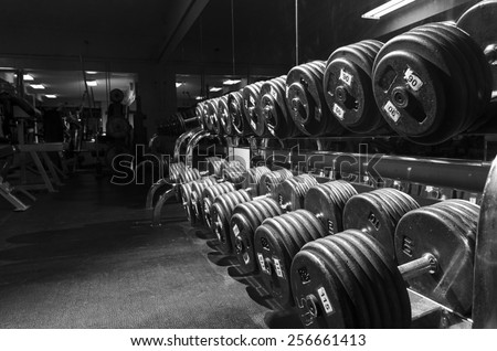 weights. Shallow depth of field, blurred foreground, focused lighting on weights for emphasis. dramatic lighting. blurred background. dust on gym mirror and not on camera sensor or lens.