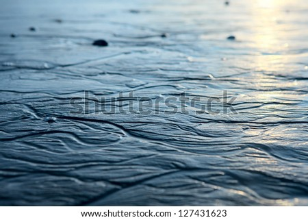 Wet sand pattern in shallow water on a beach in the morning