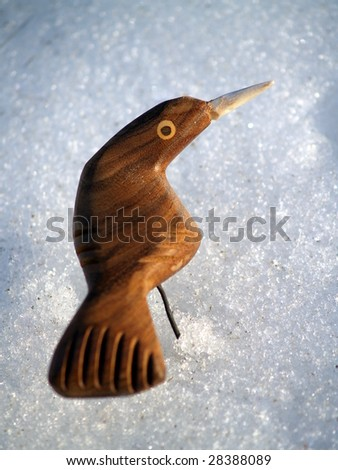 """What am I doing here?"" Carved wooden bird in the snow looks back at the camera"