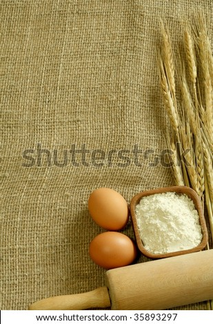 Wheat ears, flour and eggs on sacking.