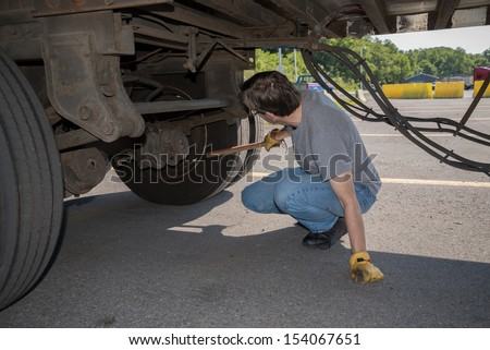 18-Wheeler Pre-trip Tire Inspection - A professional driver is using a tire thumper to check the tires underneath his trailer prior to driving OTR.   Imagine de stoc ©