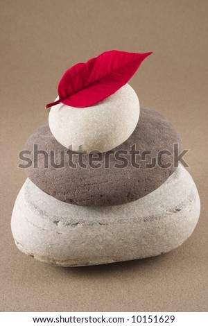 3 white and grey balancing pebbles with a red leaf on the top - stock photo