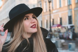 1 white beautiful blonde woman in a black wide brimmed hat on the street